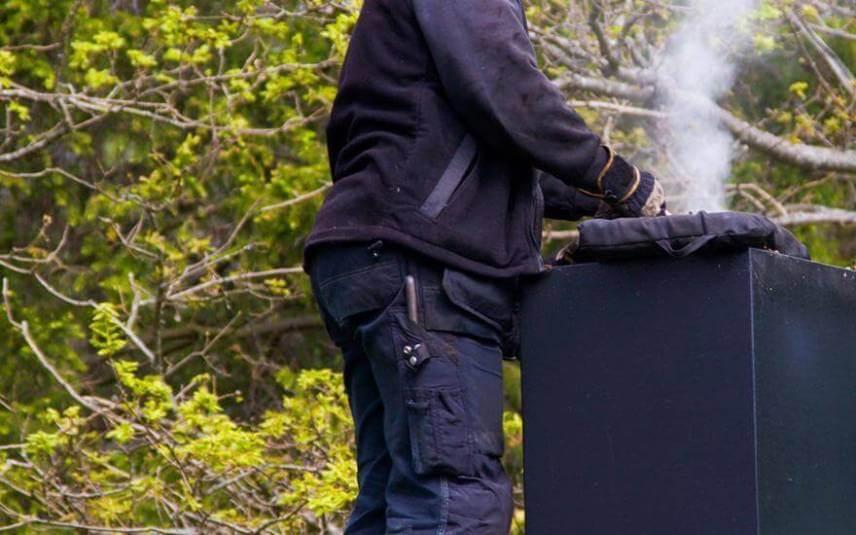 Kominiarz czyszczący komin
